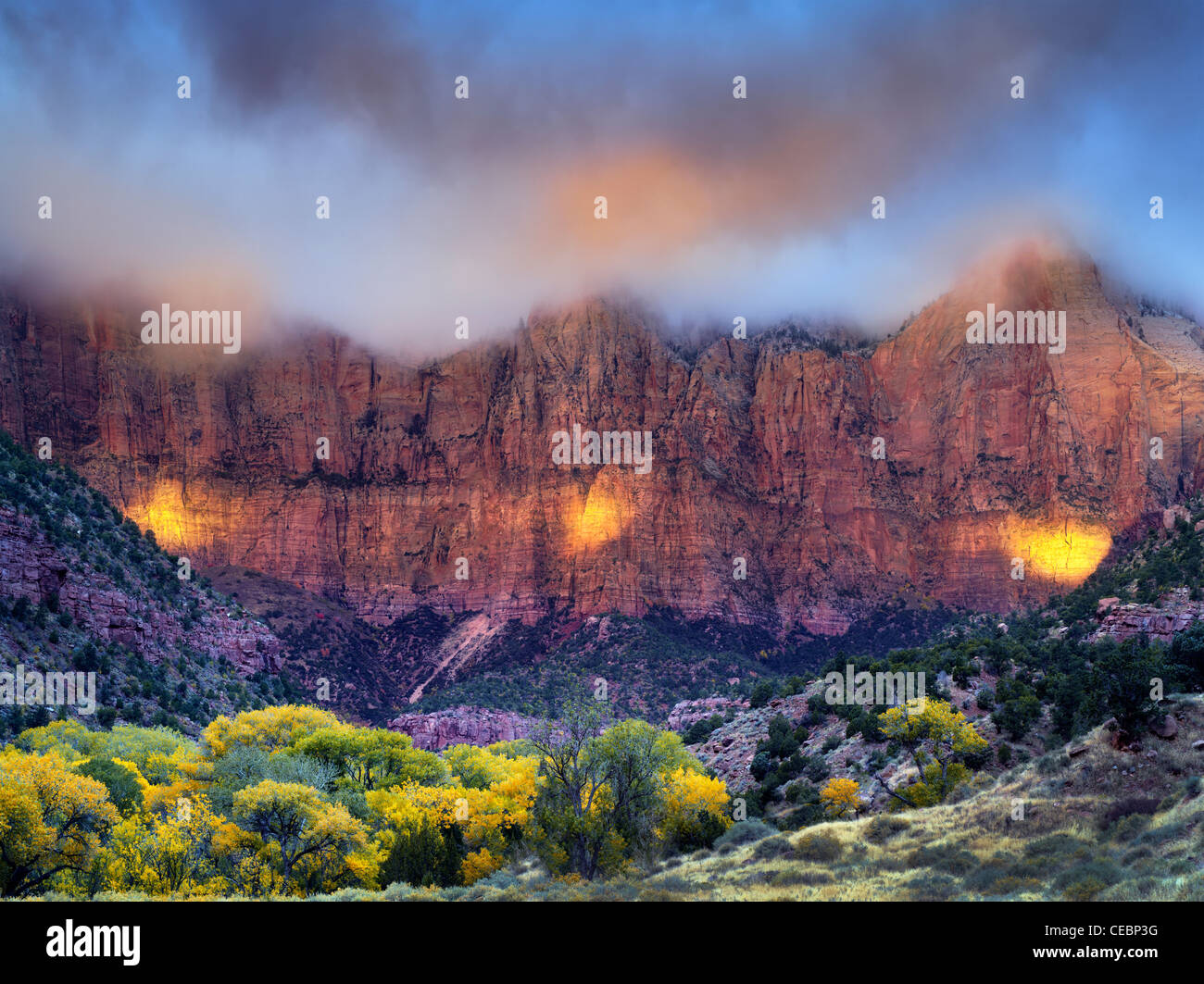 Sunrise peaking through storm clouds.with fall color Towers of the Virgin. Zion National Park, Utah - Stock Image