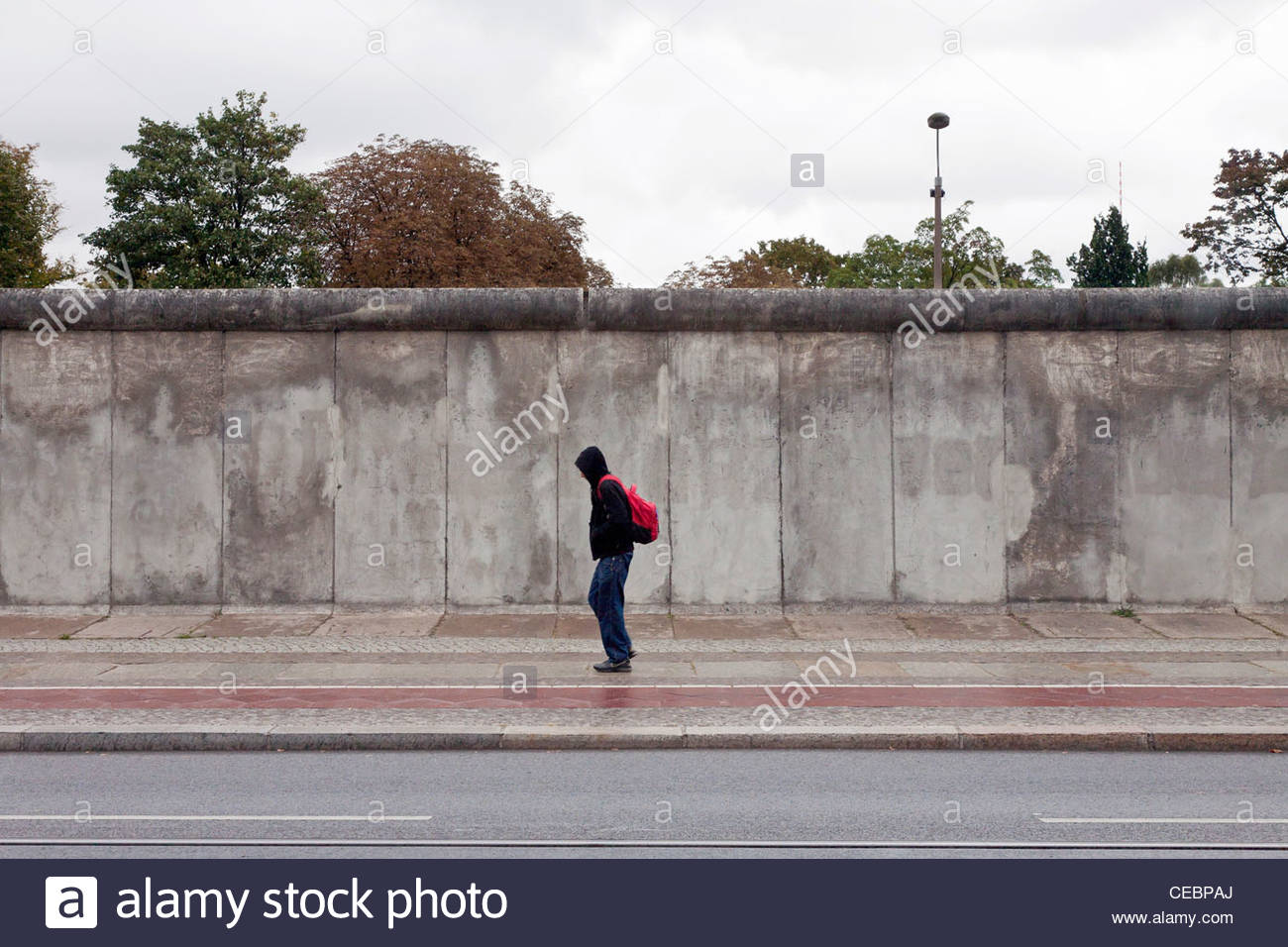 Person passing in front of a preserved section of the Berlin Wall in front of the Berlin Wall Memorial, Berlin, - Stock Image