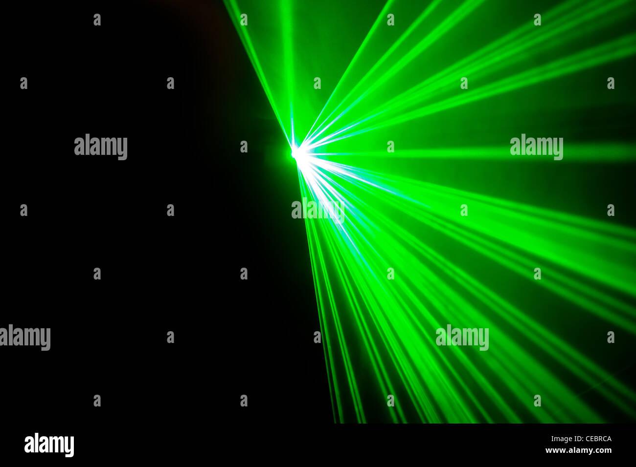 Real green laser lights on black background - Stock Image