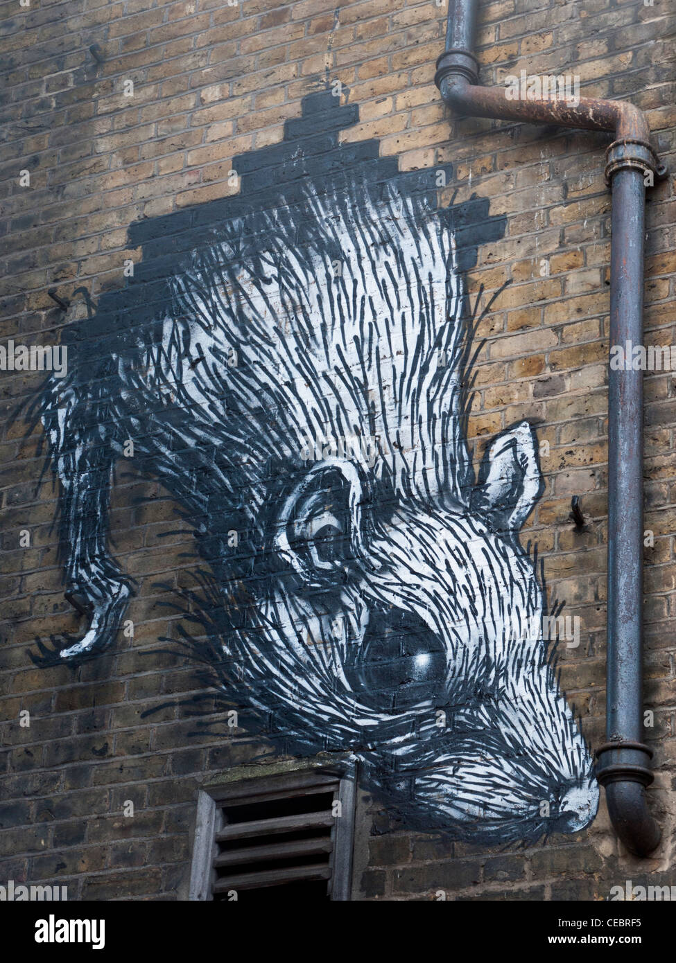 Painting of a rat on a wall in east London, England. - Stock Image