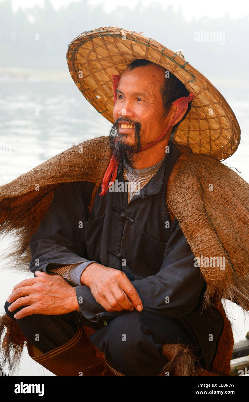 Close up of a smiling cormorant fisherman on the Li river at dawn Xingpingzhen Yangshuo, Guilin, Guangxi China Stock Photo