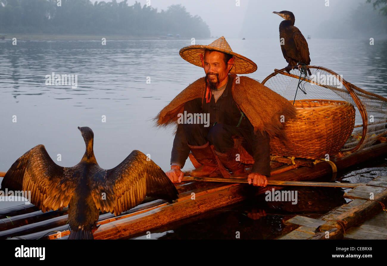 Smiling cormorant fisherman with birds on a bamboo raft on the Li river at dawn Xingpingzhen Yangshuo, Guilin, Guangxi China Stock Photo