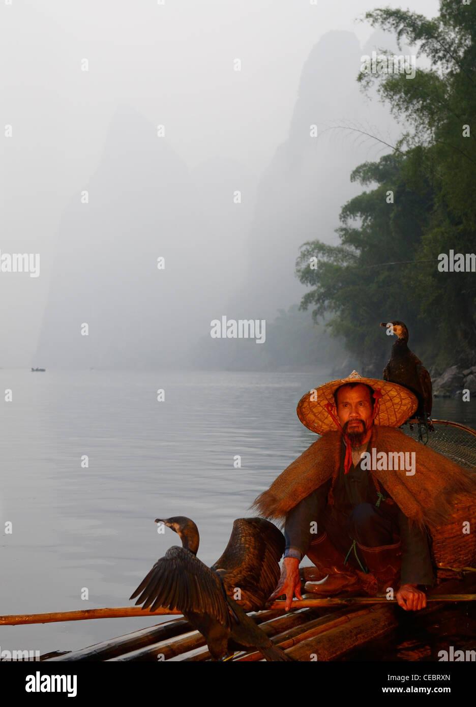 Cormorant fisherman on a bamboo raft on the Li river with Karst mountain peaks Xingpingzhen Yangshuo, Guilin, Guangxi China Stock Photo