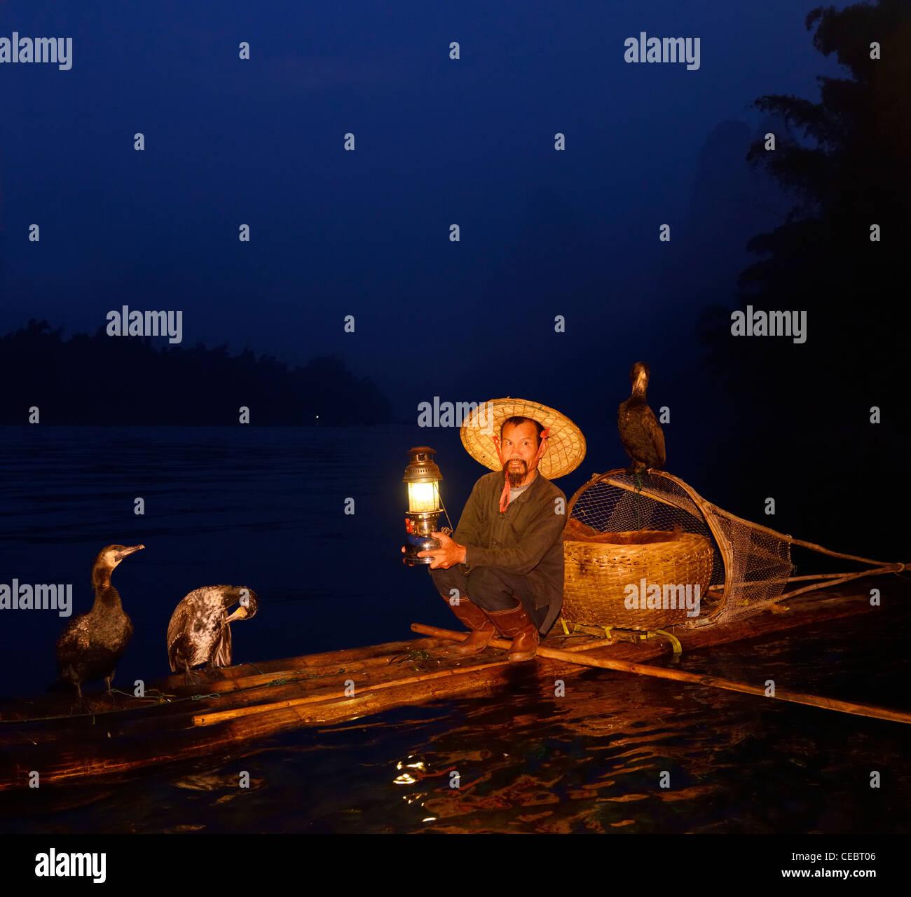 Cormorant fisherman with lamp on bamboo raft at dawn on Li or Lijiang river Xingpingzhen Yangshuo, Guilin, Guangxi China Stock Photo