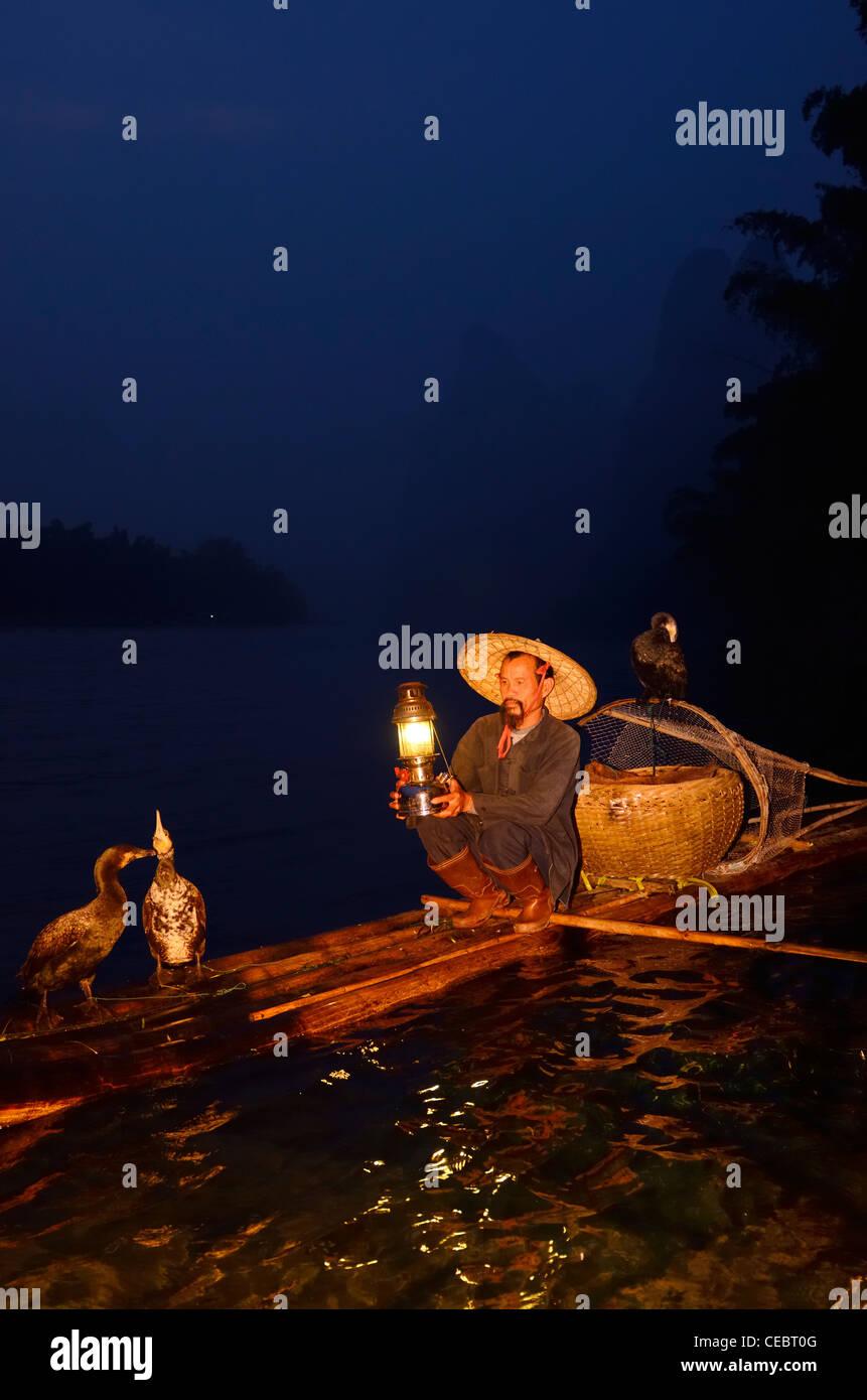Early morning Cormorant fisherman with lamp on bamboo raft on Li or Lijiang river Xingpingzhen Yangshuo, Guilin, Guangxi China Stock Photo