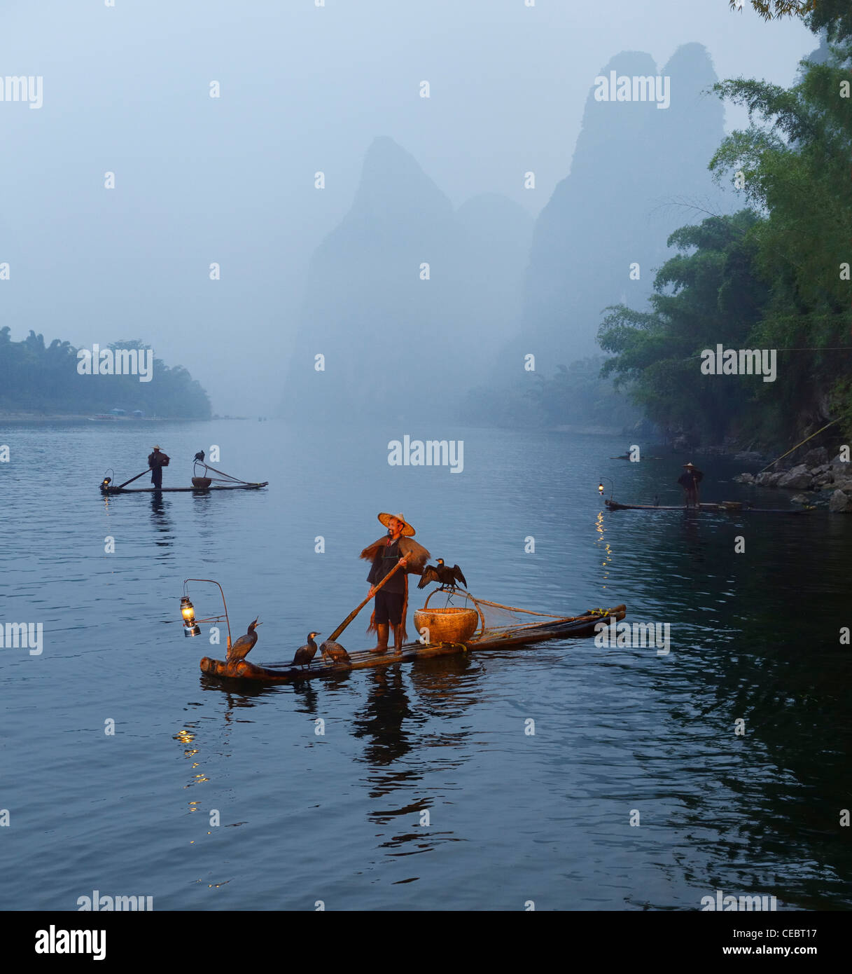 Cormorant fishermen in mist at dawn on the Li river with Karst mountain peaks near Xingping China Stock Photo