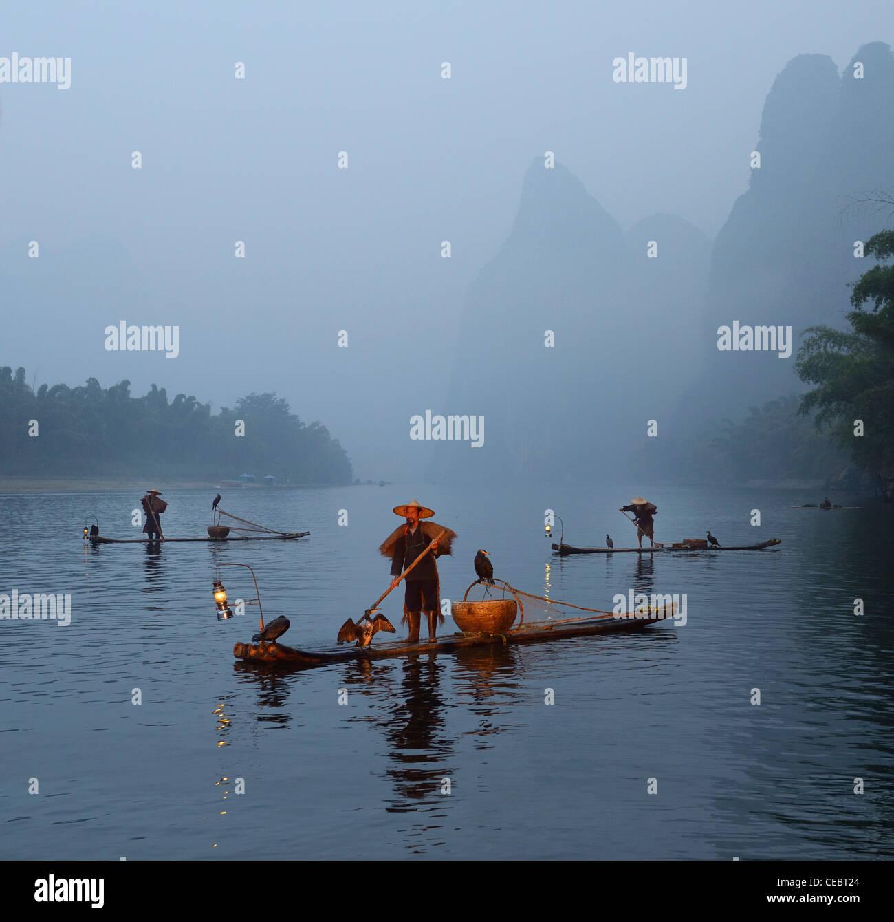 Cormorant fishermen on the Li river at dawn with Karst mountain peaks in mist Xingpingzhen Yangshuo, Guilin, Guangxi China Stock Photo