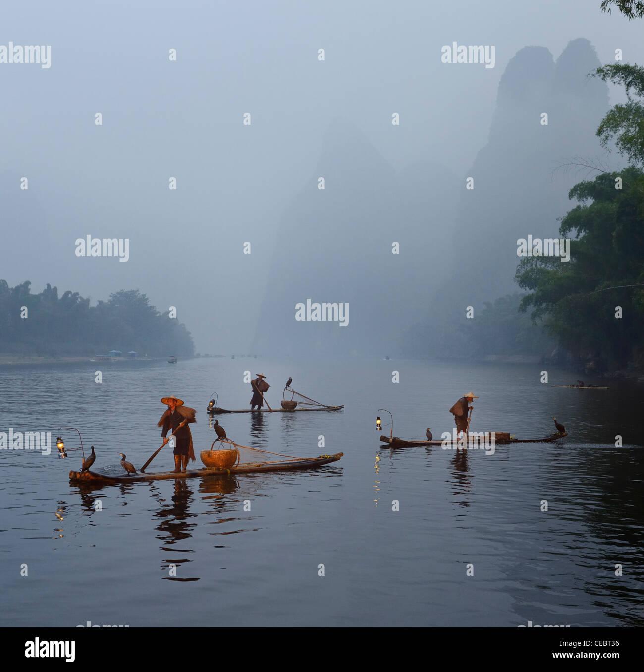 Cormorant fishermen in morning mist on the Li river with Karst mountain peaks Xingpingzhen Yangshuo, Guilin, Guangxi China Stock Photo