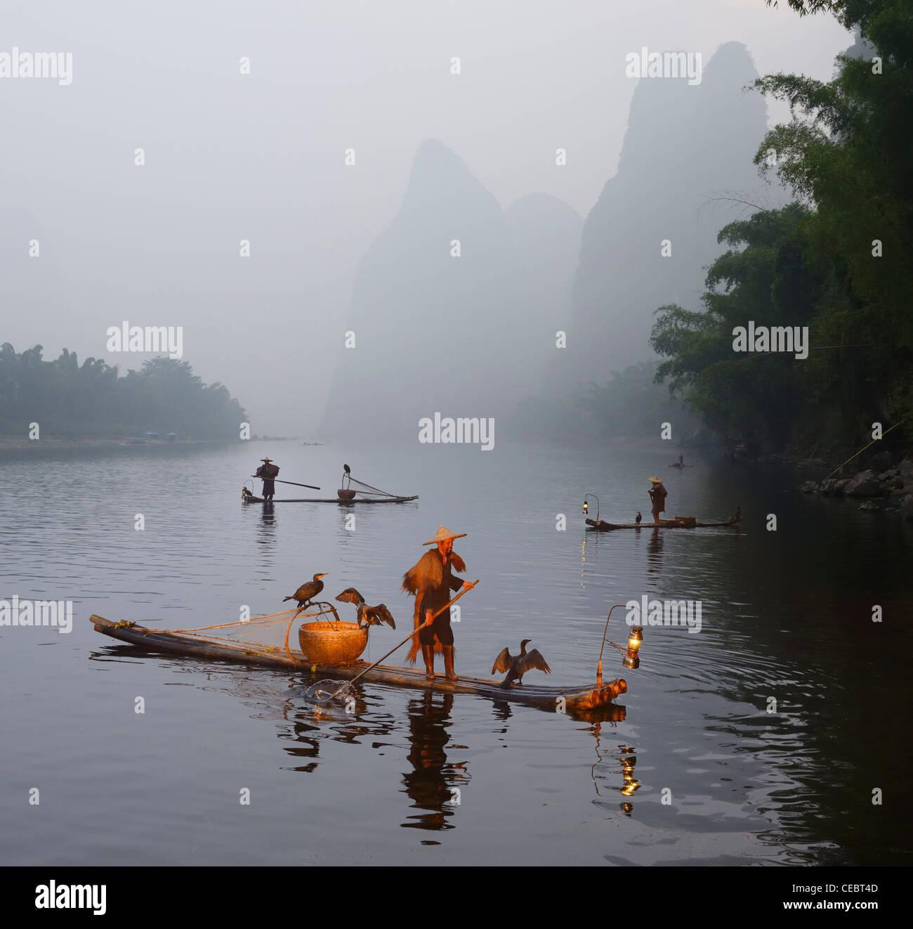 Cormorant fishermen paddling bamboo raft at dawn on the Li river with Karst mountain peaks Xingpingzhen Yangshuo, Guilin, Guangxi China Stock Photo