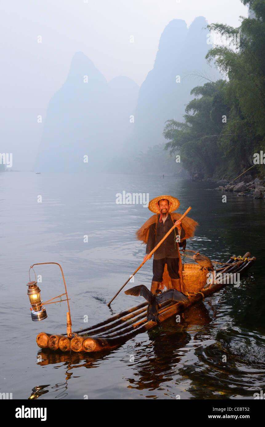 Cormorant fisherman paddling bamboo raft on the Li river with Karst mountain peaks Xingpingzhen Yangshuo, Guilin, Guangxi China Stock Photo