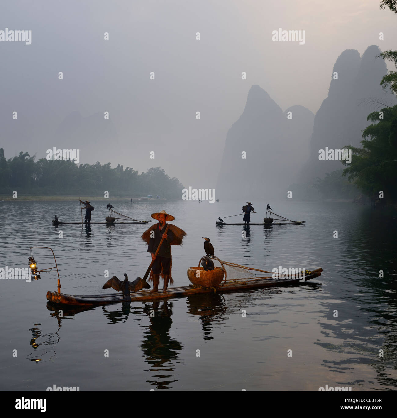 Cormorant fishermen in bamboo rafts at sunrise on the Li river with Karst mountain peaks near Xingping China Stock Photo