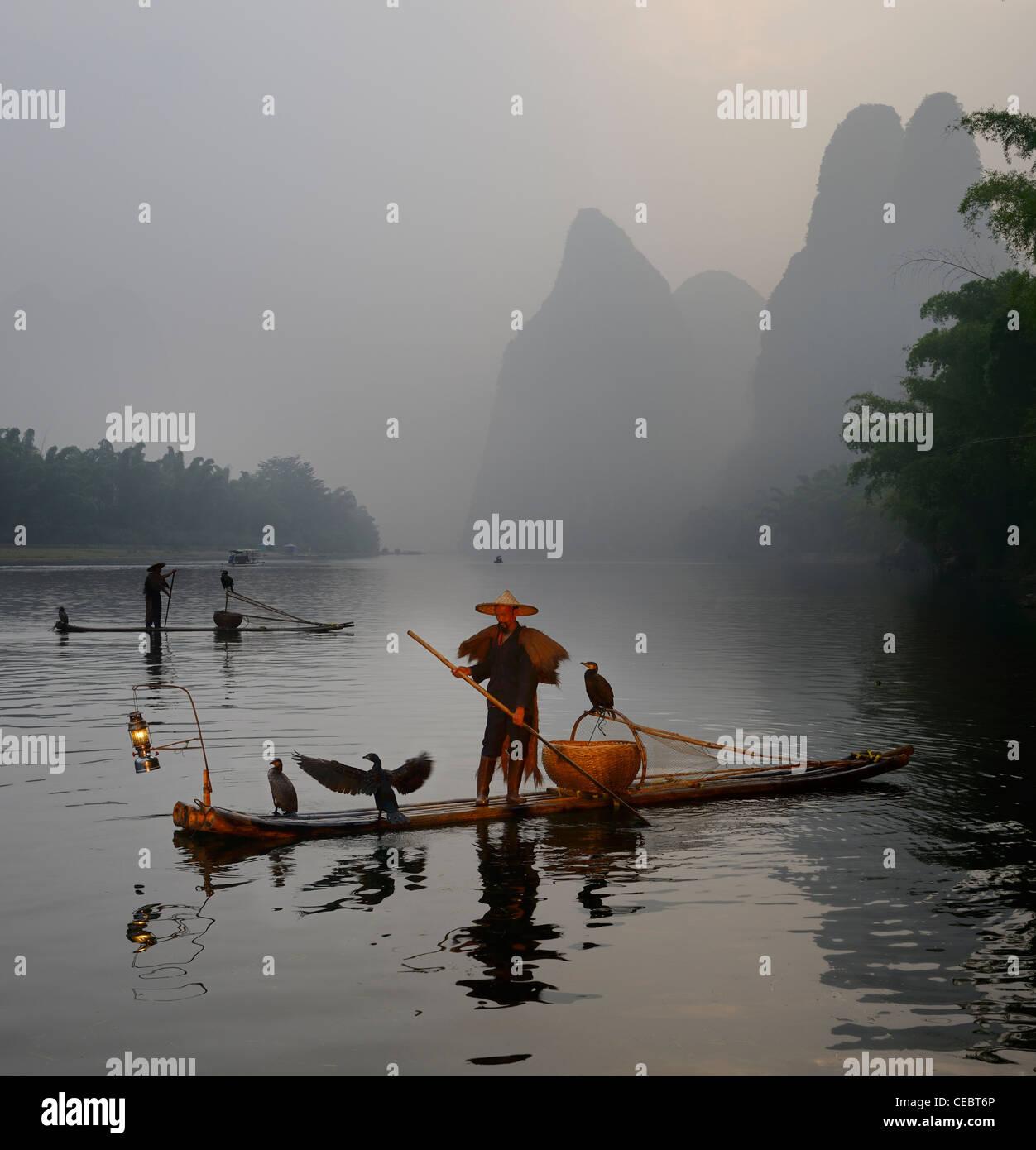 Cormorant fishermen paddling bamboo rafts at dawn on the Li river with Karst mountain peaks Xingpingzhen Yangshuo, Guilin, Guangxi China Stock Photo