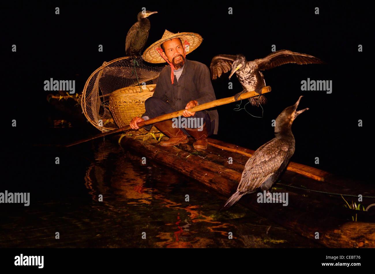 Cormorant fisherman holding bird on a pole on a bamboo raft on the Li or Lijiang river at night Xingpingzhen Yangshuo, Guilin, Guangxi China Stock Photo