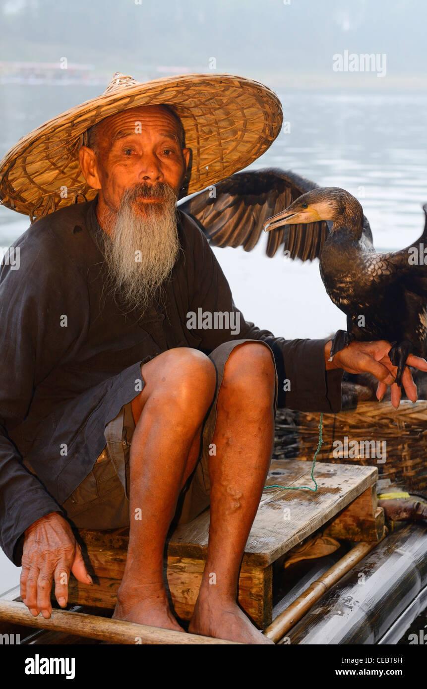 Cormorant fisherman holding bird on a bamboo raft on the Li river Huangbutan China Stock Photo