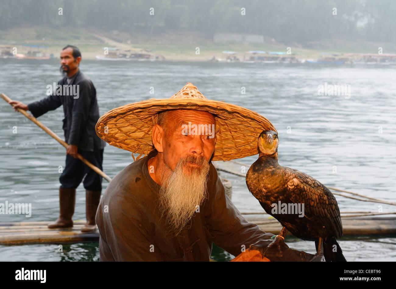 Cormorant fisherman holding bird and another paddling past on the Li or Lijiang river near Xingpingzhen Yangshuo, Guilin, Guangxi China Stock Photo