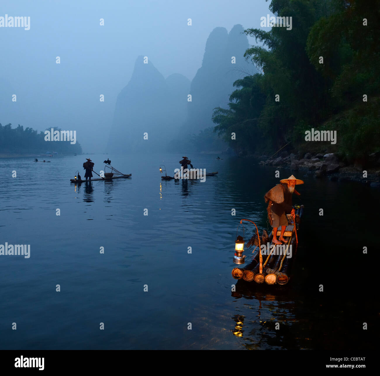 Early morning Cormorant fishermen on bamboo rafts on Li river near Xingpingzhen Yangshuo, Guilin, Guangxi China Stock Photo