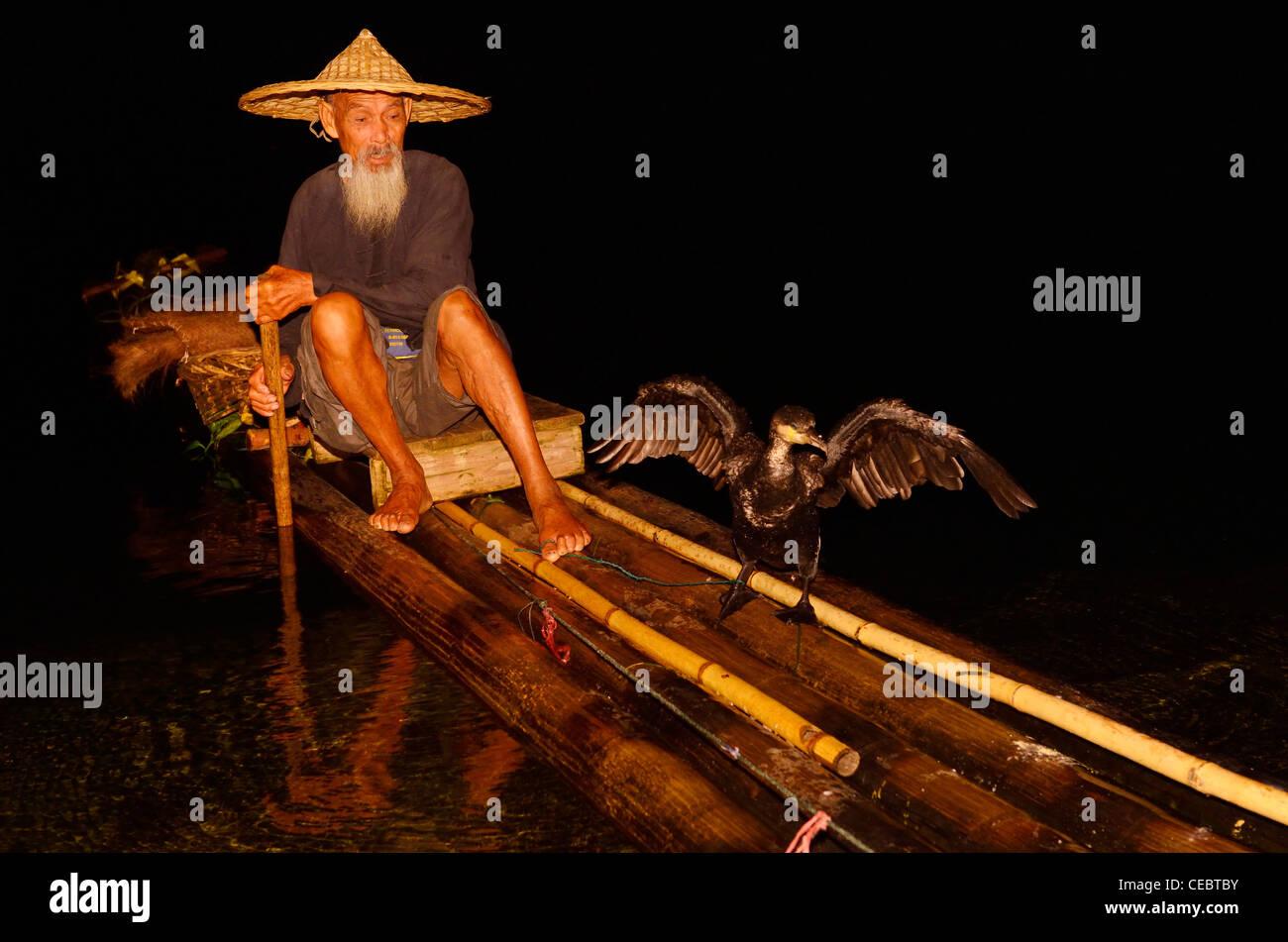 Cormorant fisherman holding bird on a string on a bamboo raft on the Li river at night Xingpingzhen Yangshuo, Guilin, Guangxi China Stock Photo