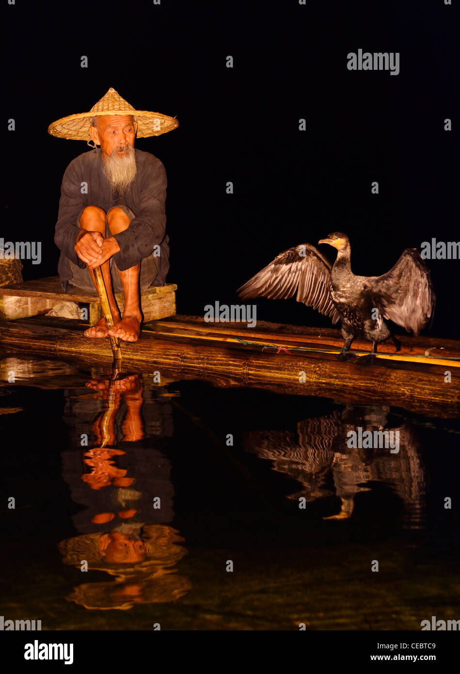 Cormorant fisherman and bird with spread wings reflected in the Li river at night from a bamboo raft Xingpingzhen Yangshuo, Guilin, Guangxi China Stock Photo