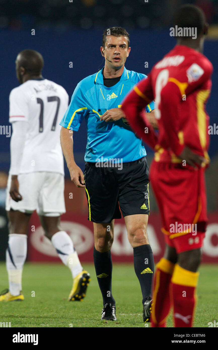 Referee Viktor Kassai reaches for a yellow card to book Jonathan Mensah of Ghana during a FIFA World Cup round of - Stock Image
