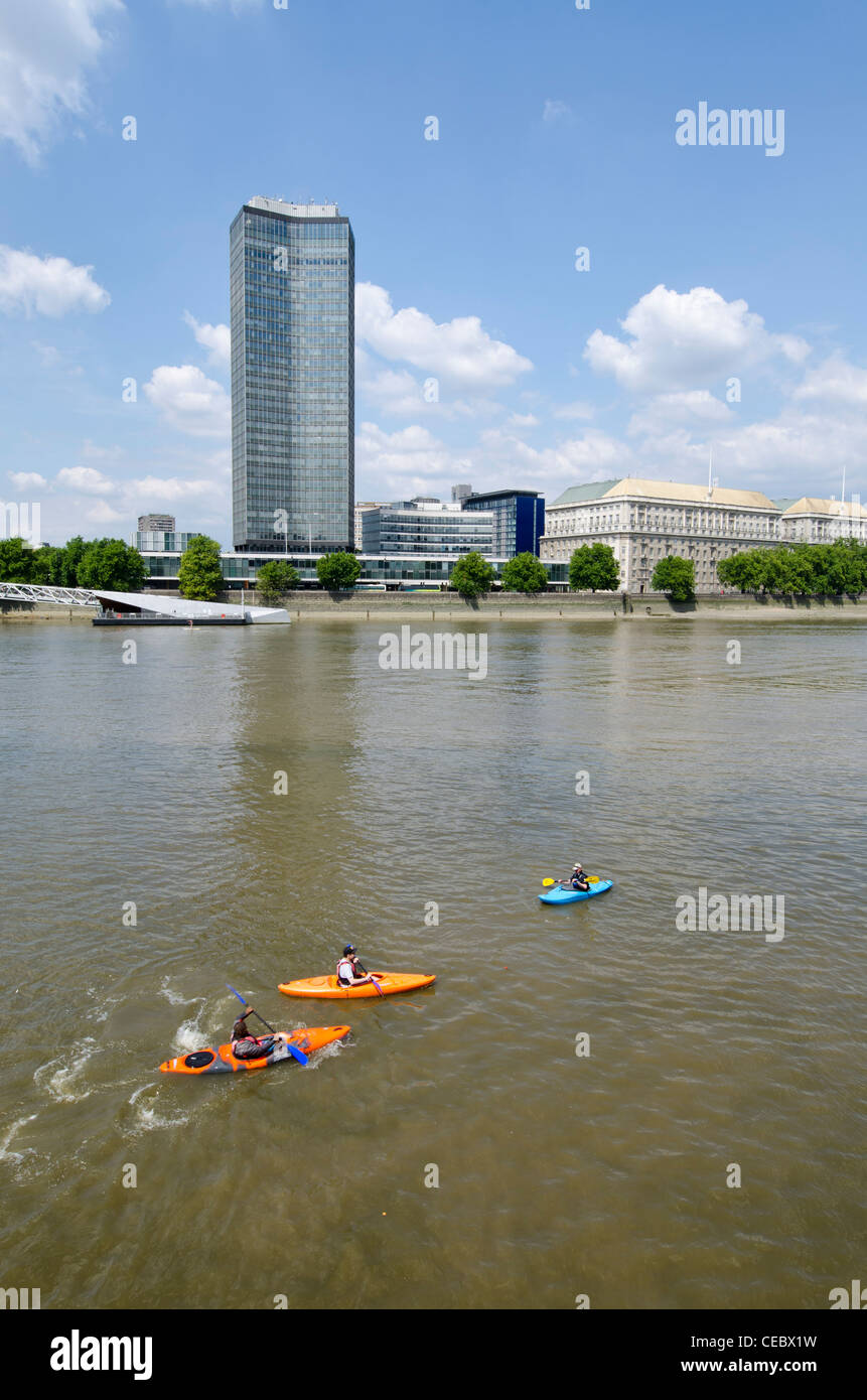 3 kayakers opposite Millbank Tower river Thames London Uk - Stock Image
