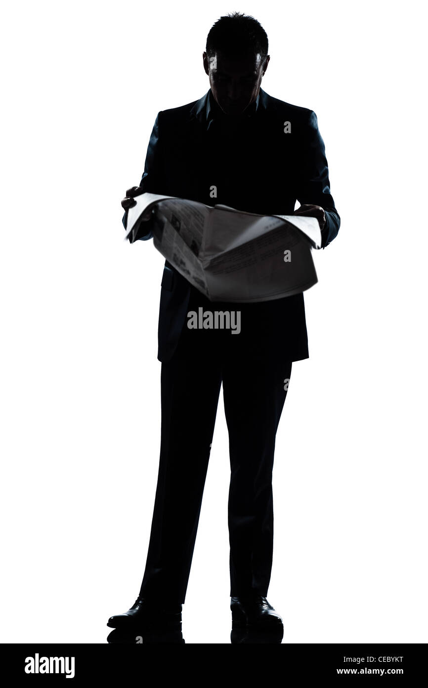 one caucasian man standing reading newspaper  full length silhouette in studio isolated white background - Stock Image