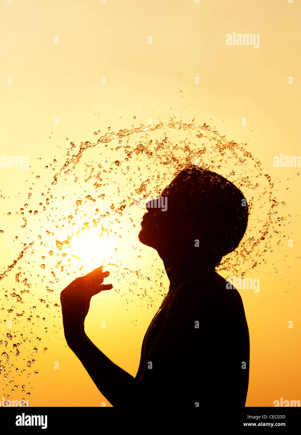 Indian man splashing water over himself at sunset. Silhouette. India - Stock Image