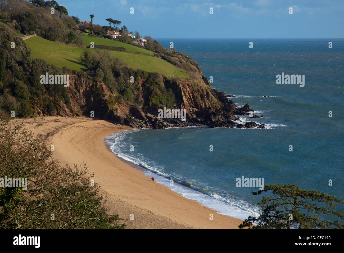 couple walking along Blackpool Sands beach, South Hams, South Devon, England. - Stock Image