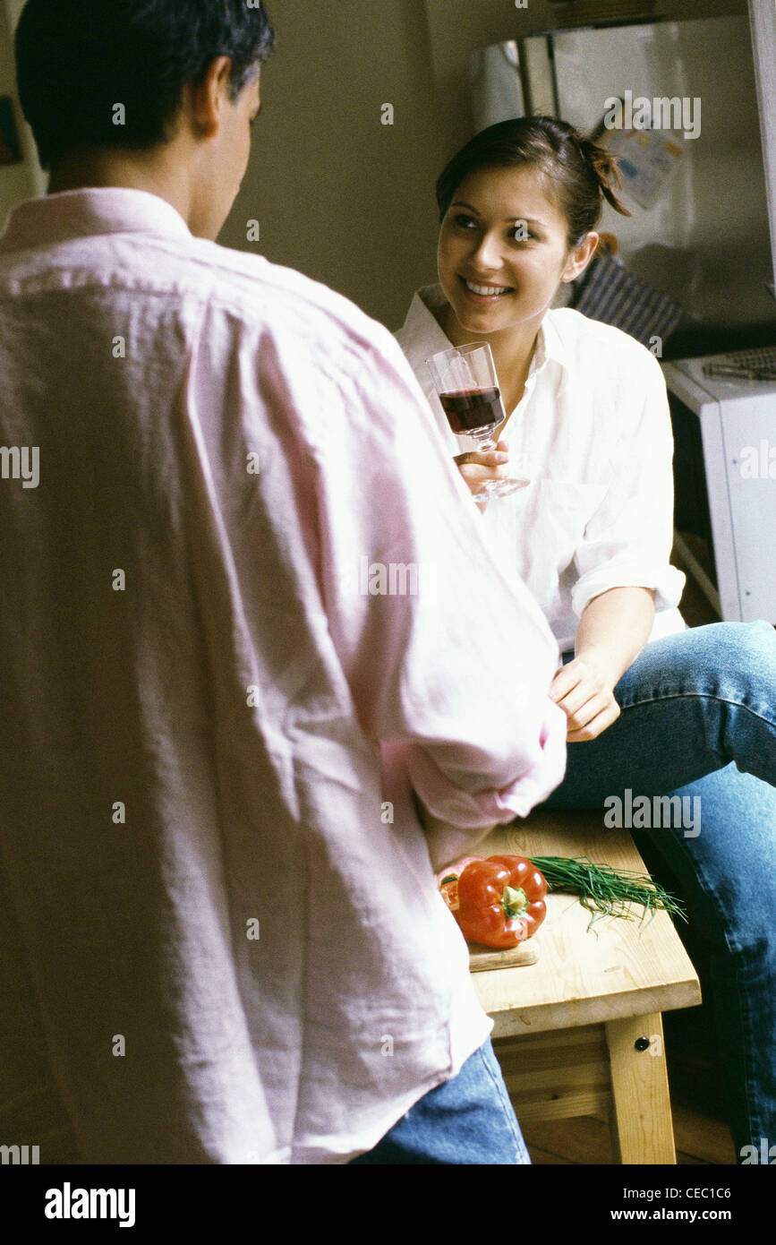 Couple together in kitchen, woman holding glass of wine - Stock Image