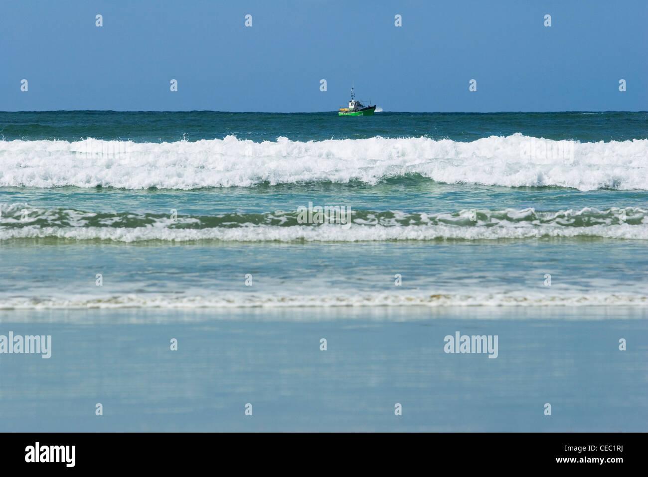 Sea shore, fishing boat on horizon Stock Photo