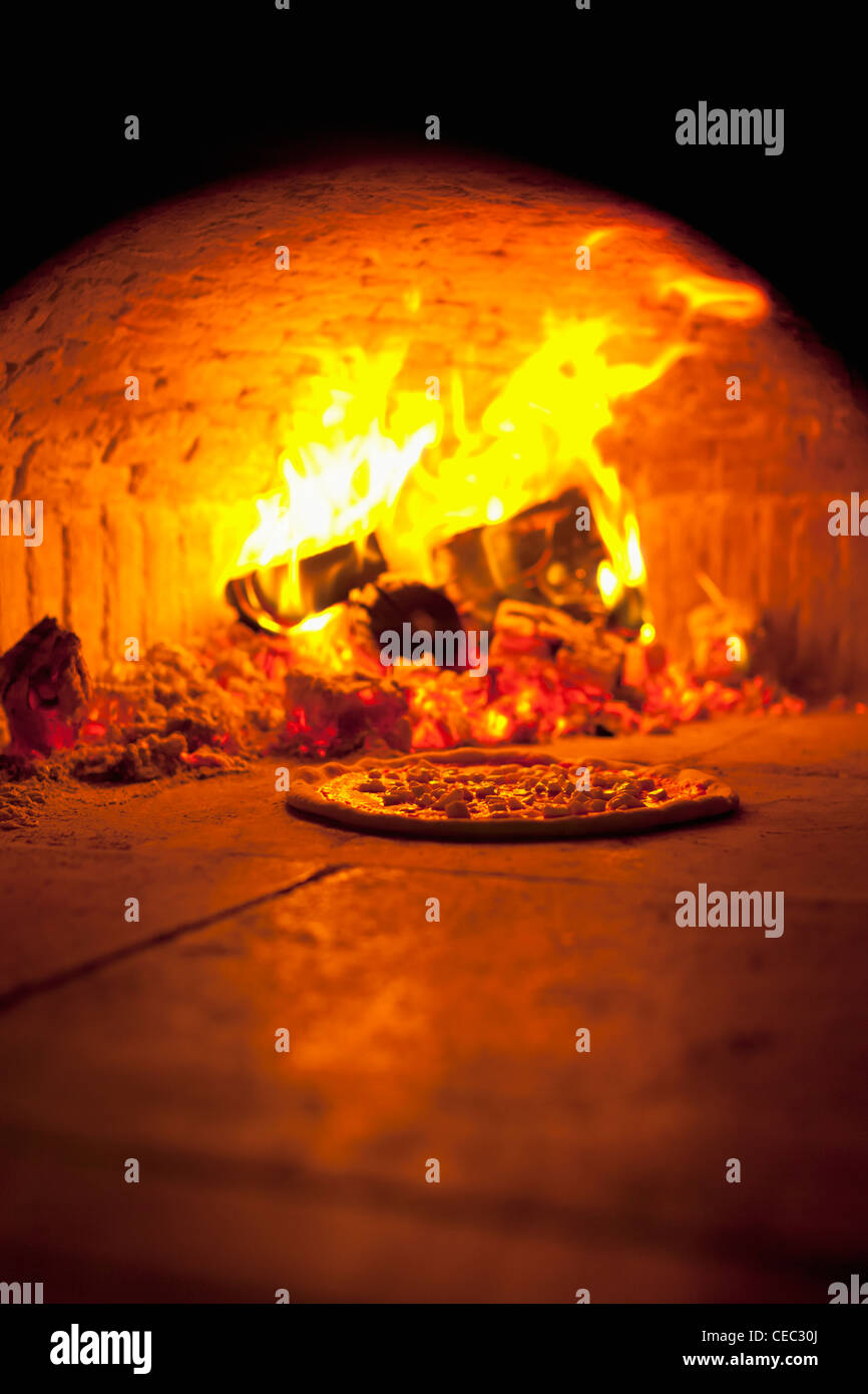 Pizza baking in an open firewood oven - Stock Image