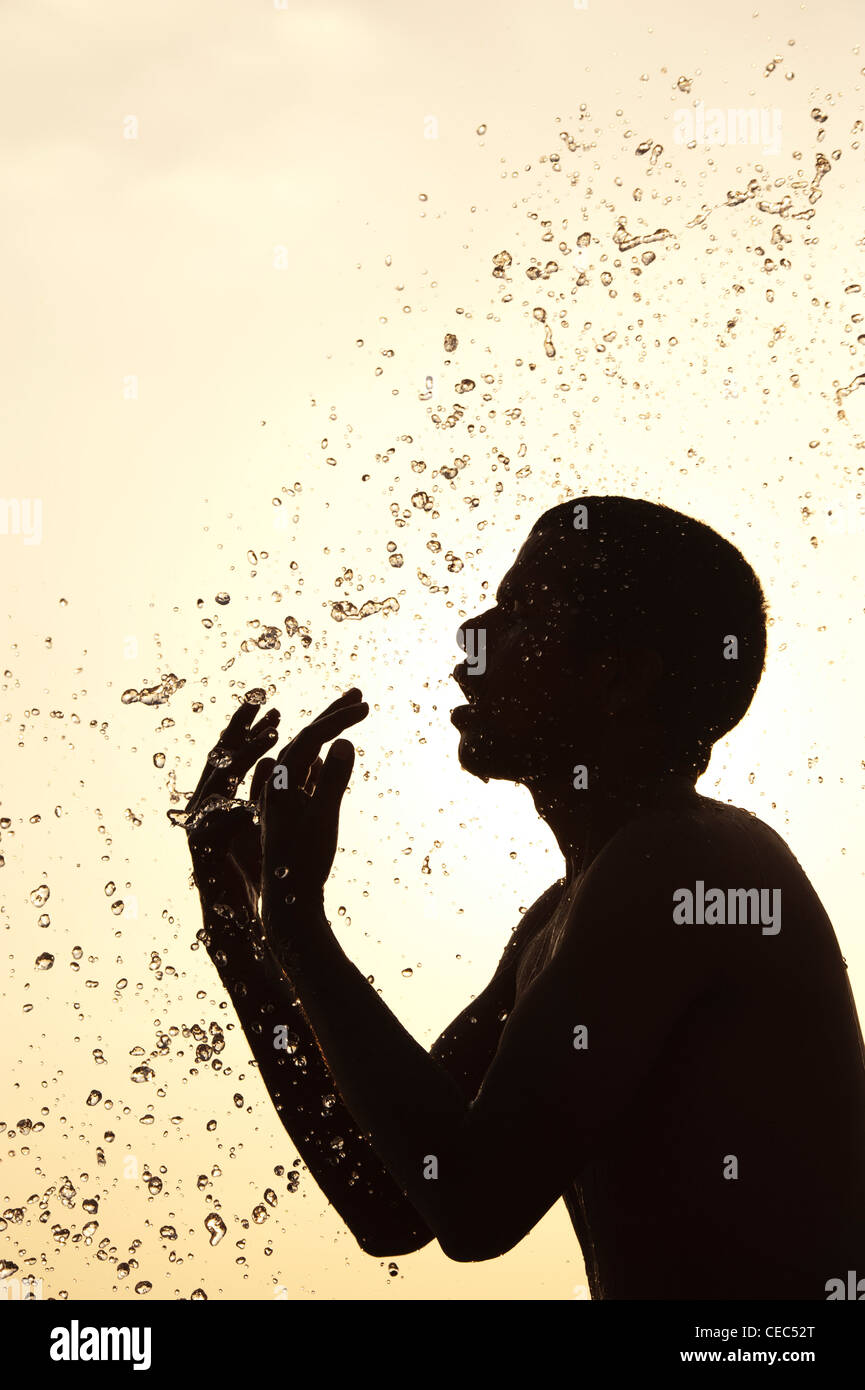 Indian man splashing water over himself. Silhouette. India - Stock Image