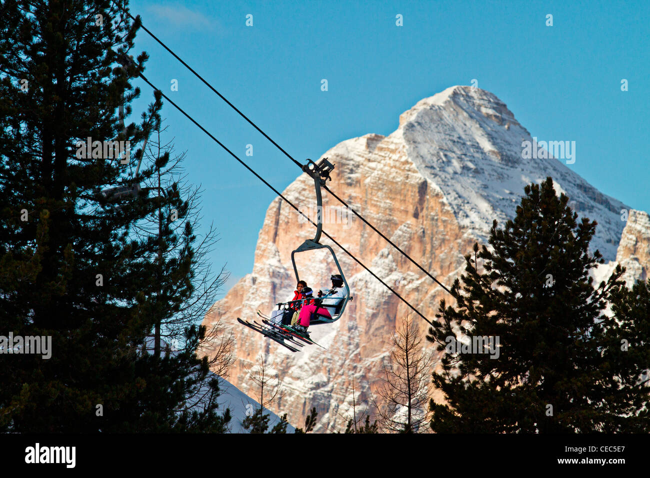 Skiers on a ski lift with Tofana di Rozes in the background, Faloria ski lift, Dolomites, Cortina d;Ampezzo, Italy - Stock Image