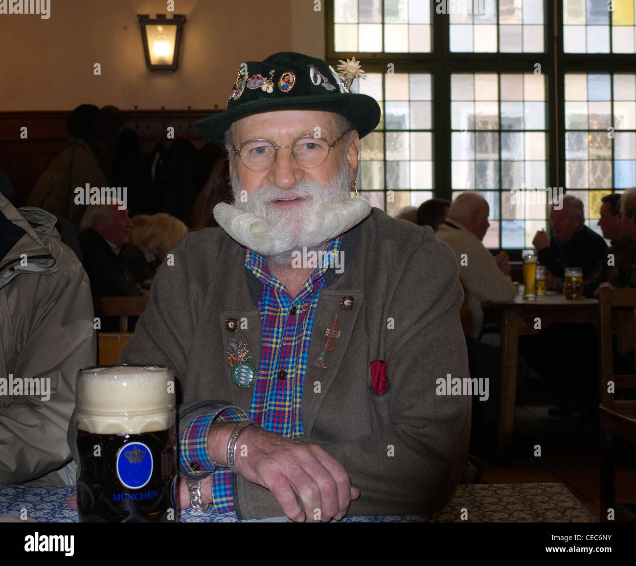 Typical Bavarian local in Hofbräuhaus drinking beer - Stock Image