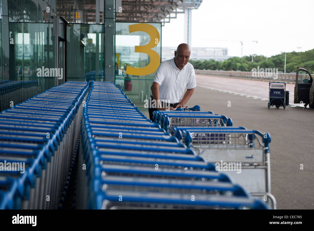 A passenger gets a baggage trolley outside the departures hall of Changi Airport terminal 3 in Singapore - Stock Image