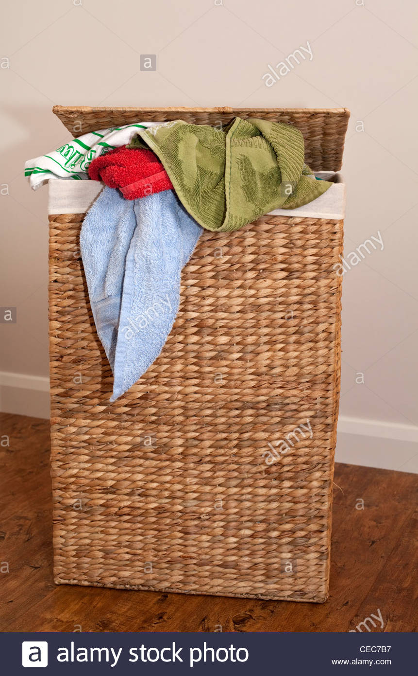 Overflowing wicker laundry basket with dirty washing spilling out - Stock Image