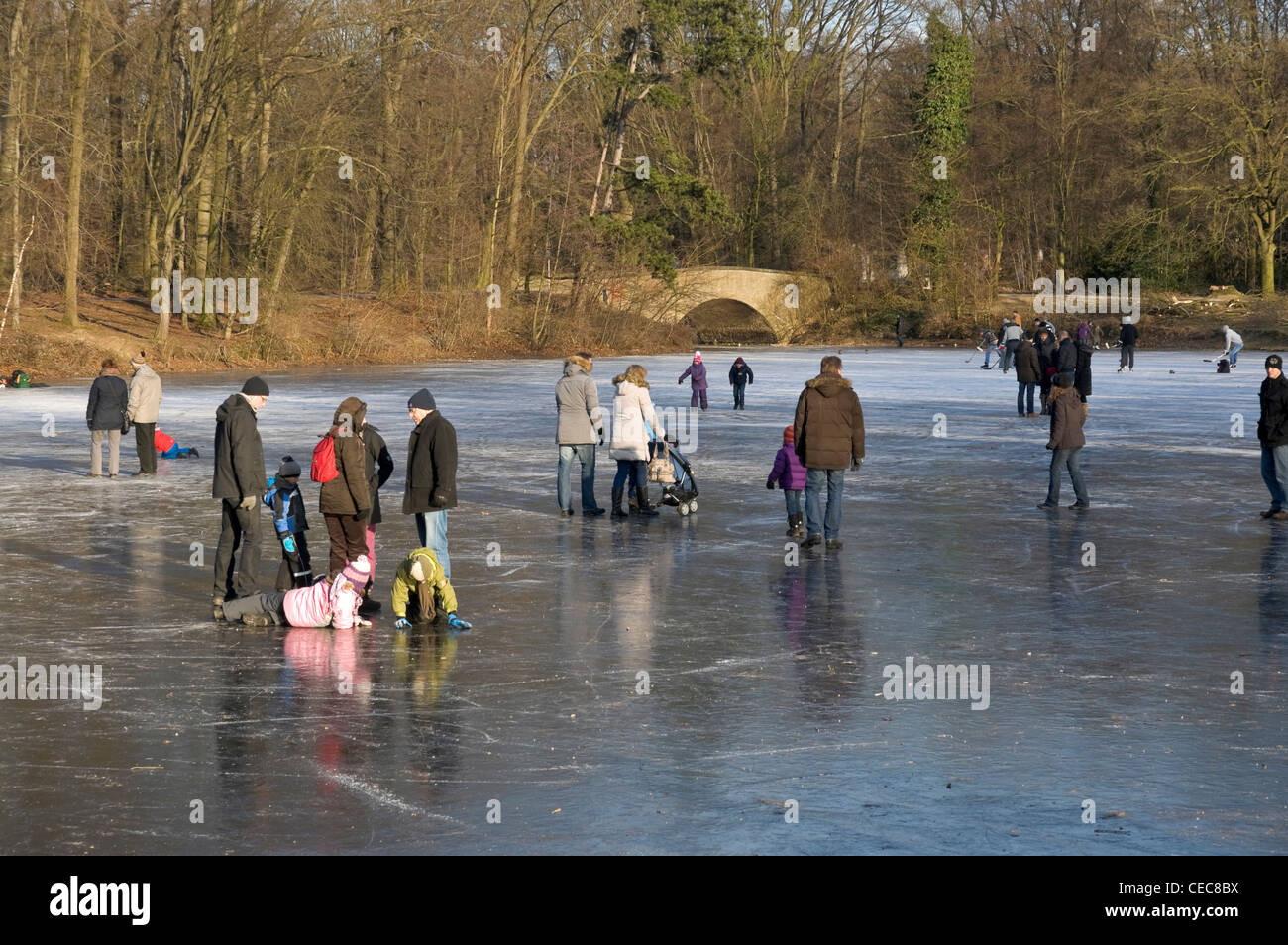 Local inhabitants enjoying a Sunday afternoon on the frozen lake in Krefeld Stadtwald park, NRW, Germany, - Stock Image