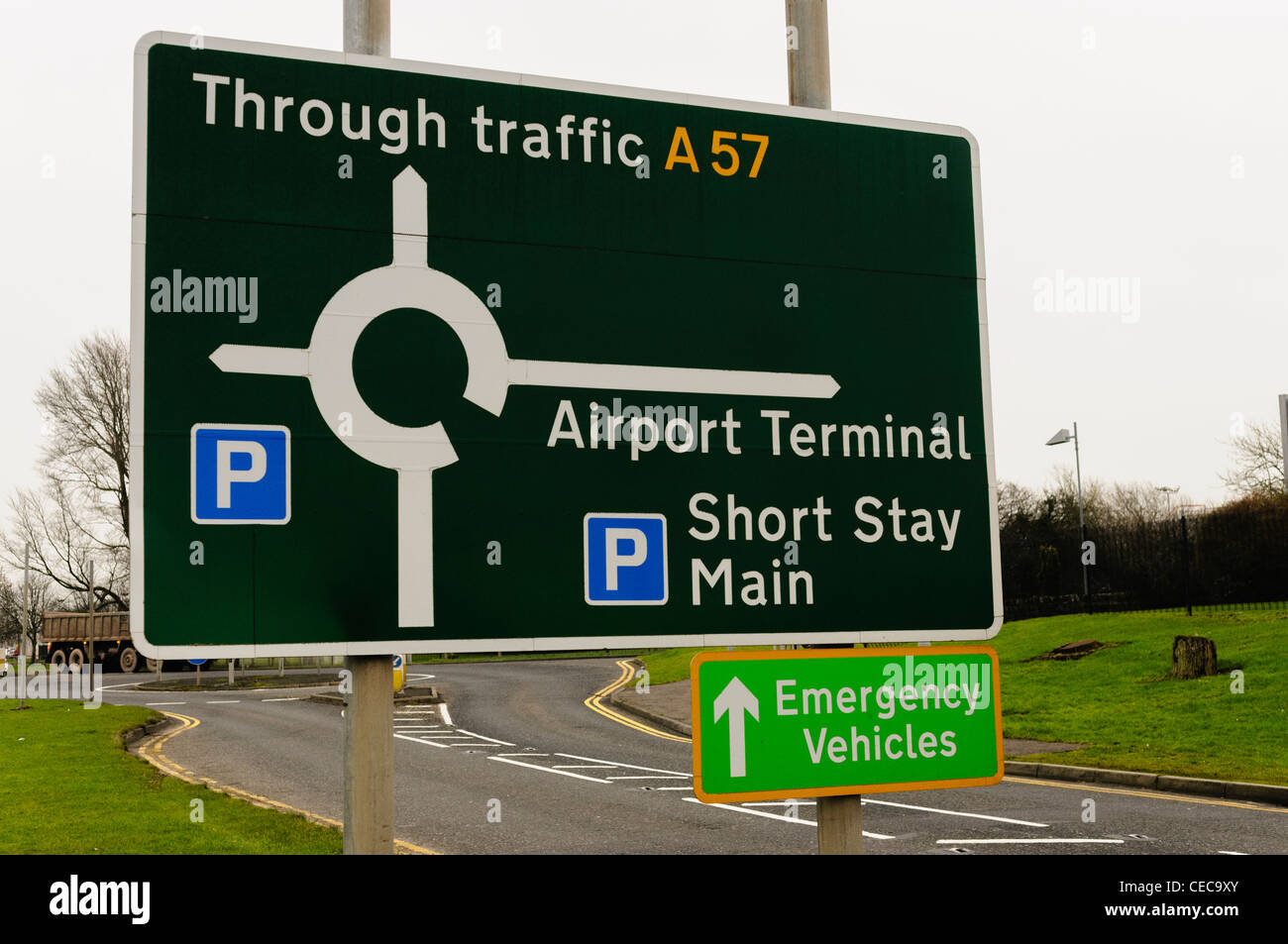 Road sign at an airport showing through traffic, terminal and parking - Stock Image