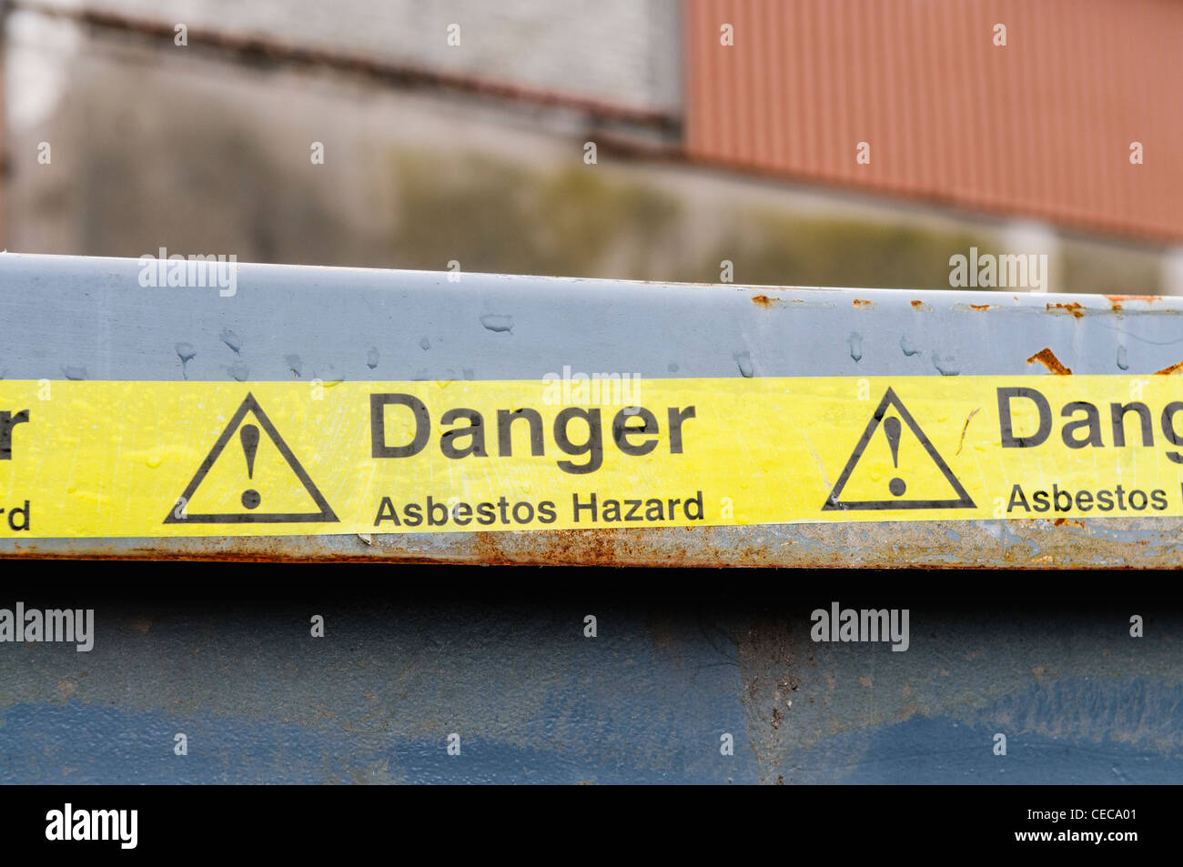 Warning tape across a bin at an Asbestos clean-up - Stock Image