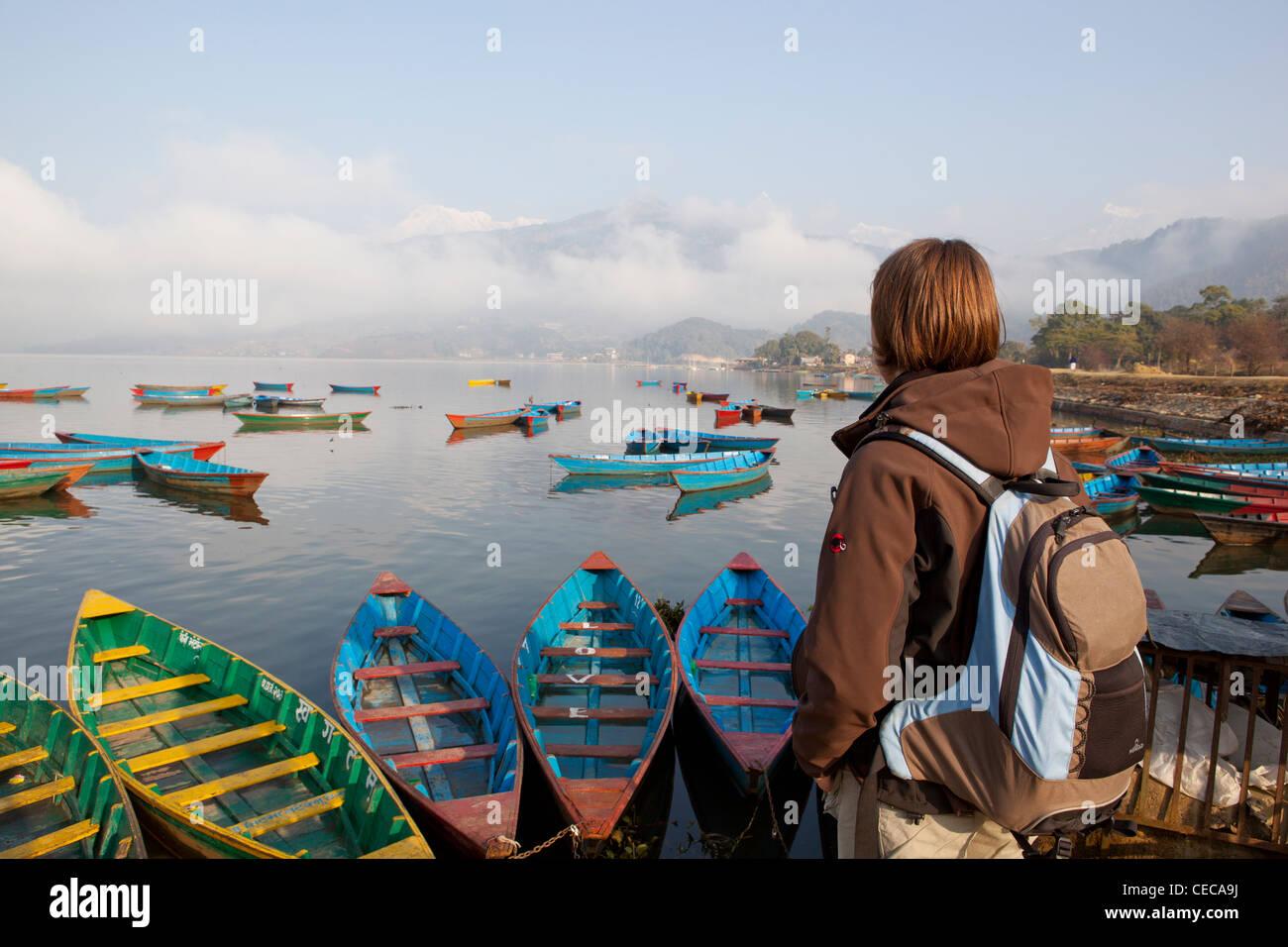 Woman overlooking colourful boats on Phewa Lake Pokhara Nepal Asia - Stock Image