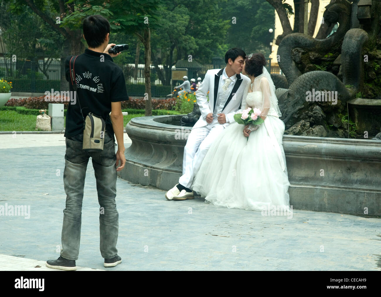 A young couple in glamorous wedding clothes poses for photos in Hanoi although this is not their wedding day - Stock Image