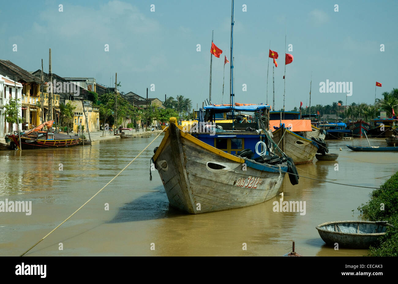 In Hoi An, a historic Vietnamese trading port, wooden fishing boats are anchored in the Thu Bon river - Stock Image