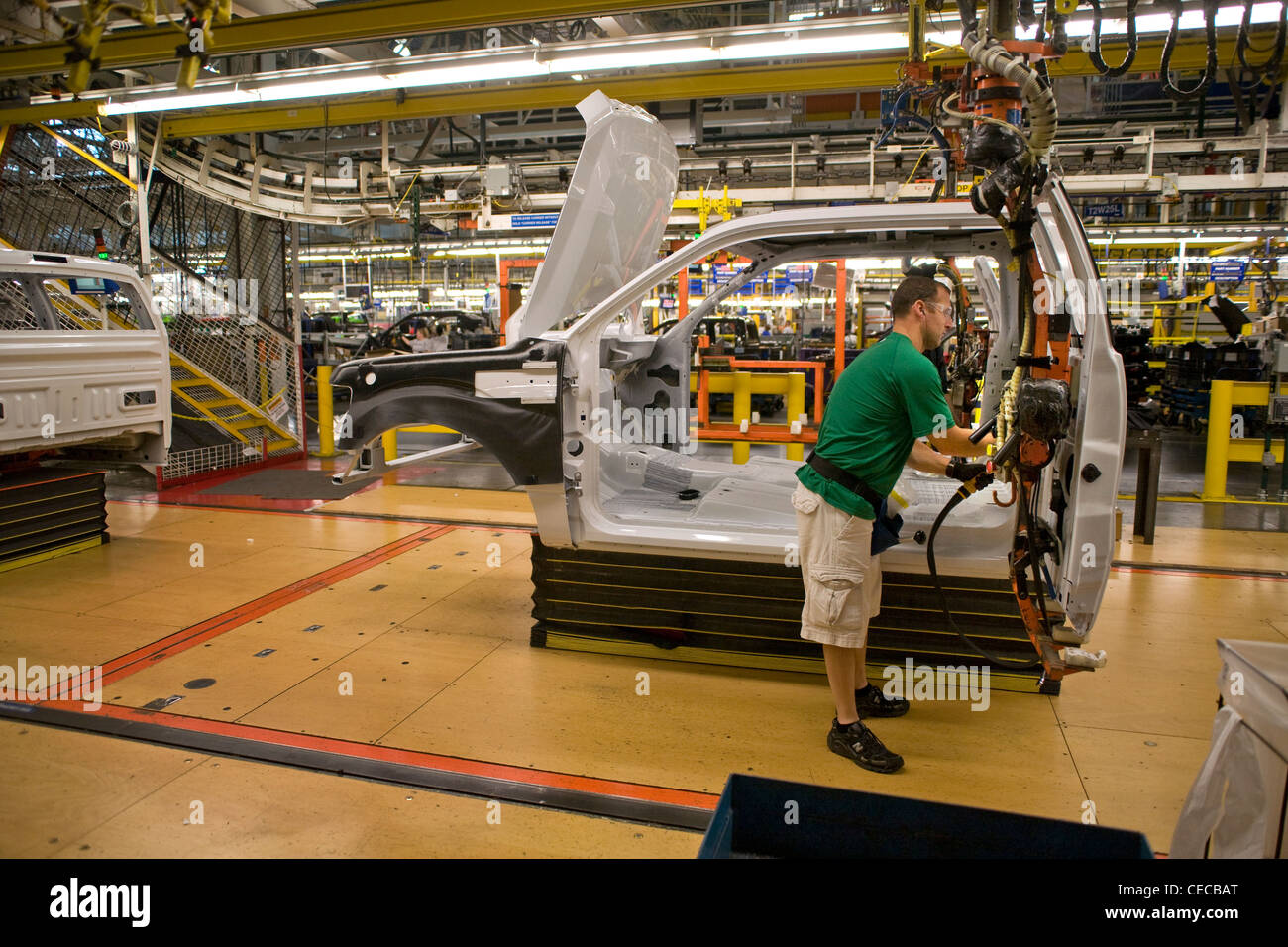 A factory worker installs door hardware on an F-150 pickup truck at the Ford final assembly plant production line - Stock Image