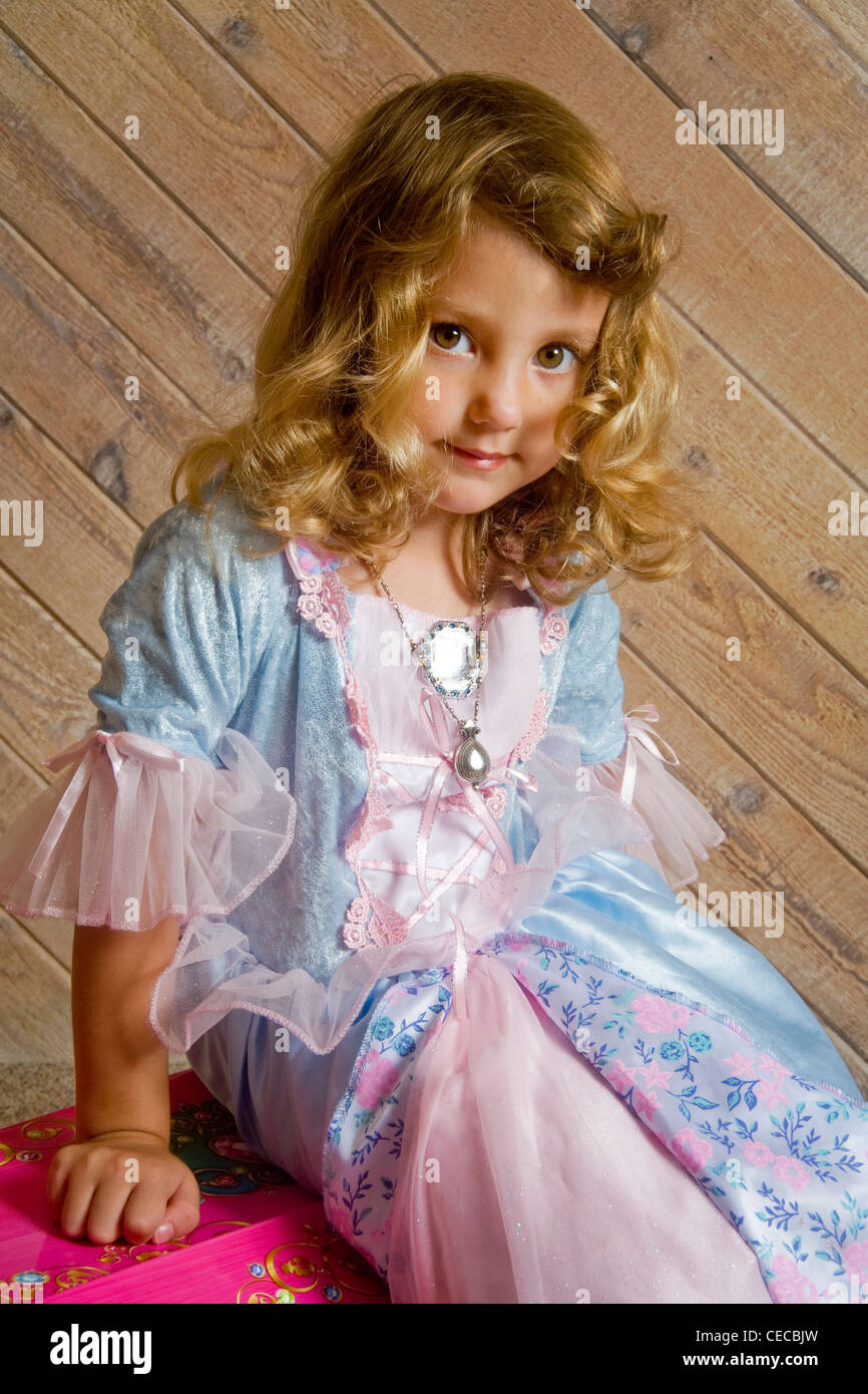 Proud but serious, a three year old blonde girl shows off fancy clothes from her treasure chest at home in Southern - Stock Image