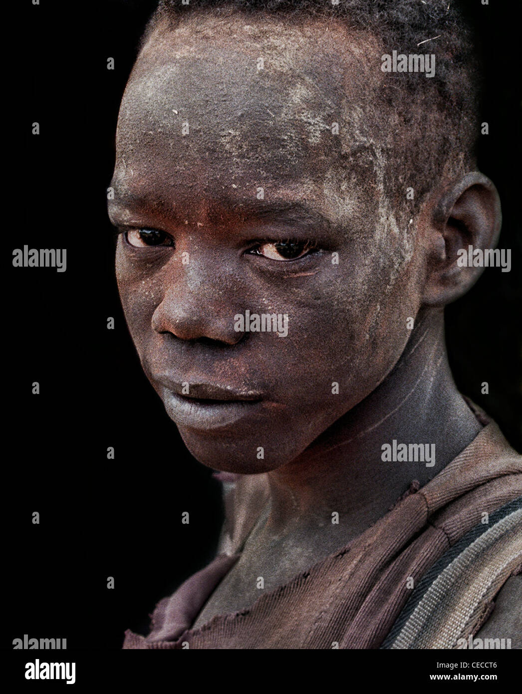 Portrait of a child soldier in Southern Sudan, his face is camouflaged to conceal his position on the front-line - Stock Image