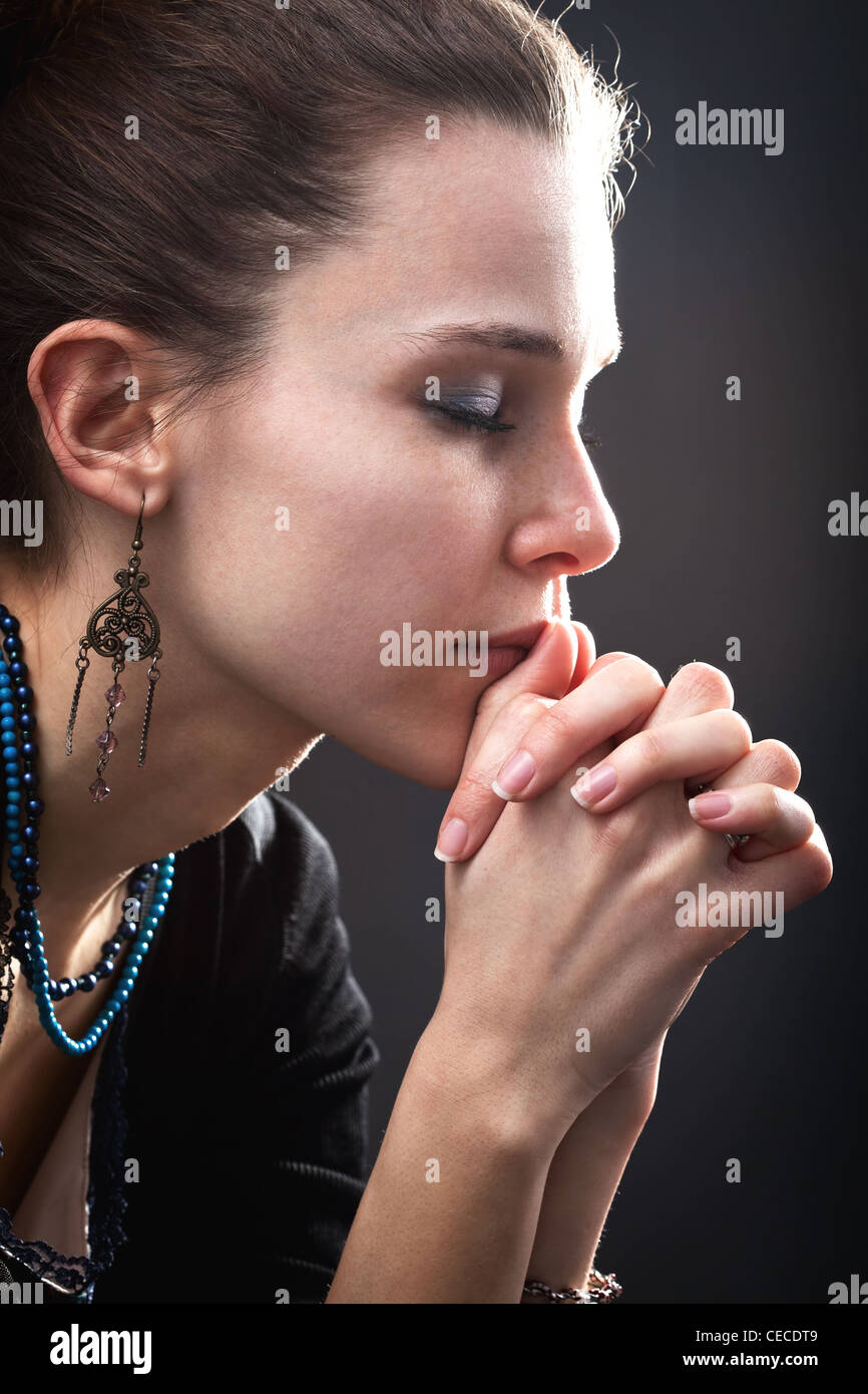 Religion concept - woman and her prayer over black - Stock Image