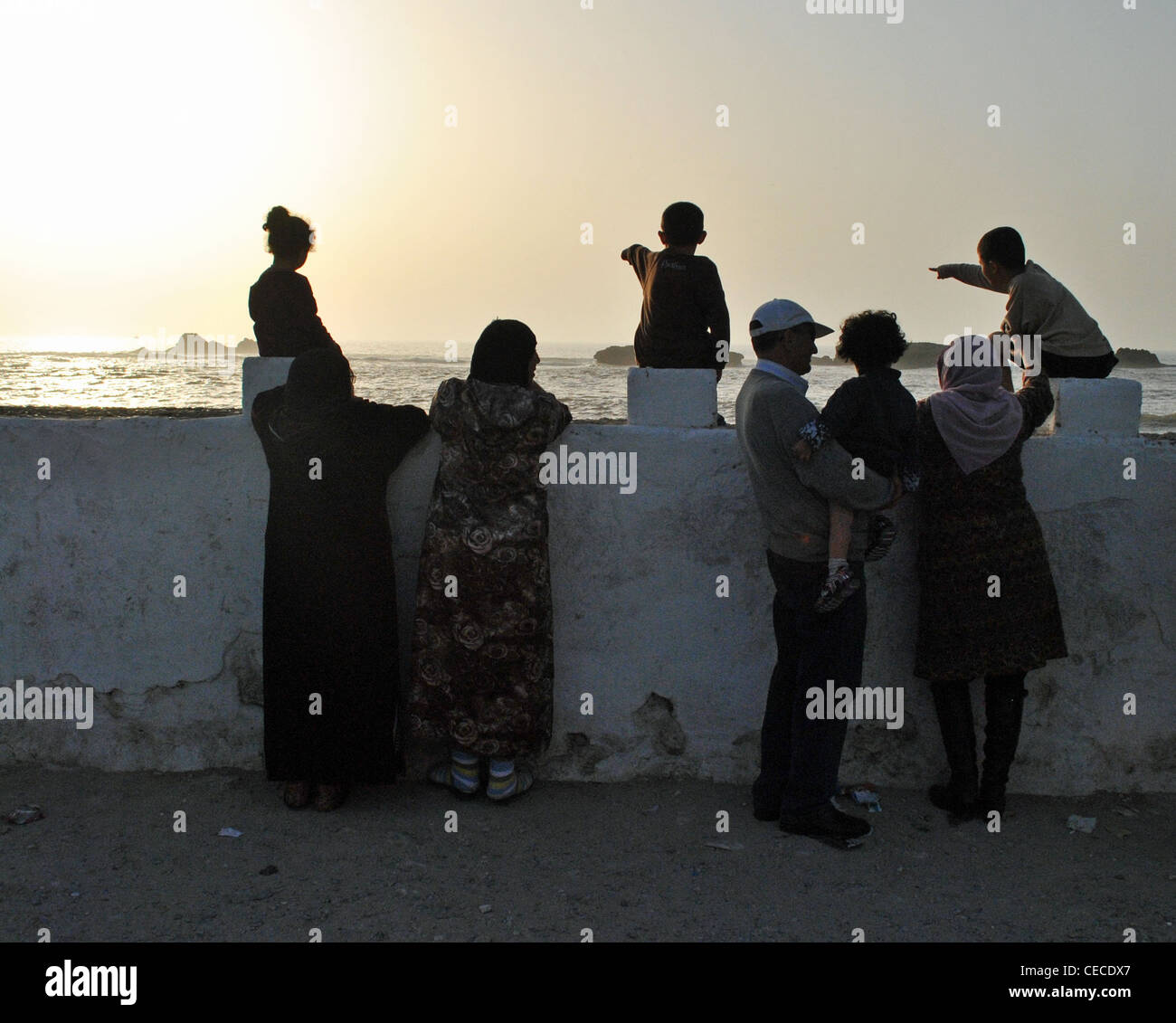 Children point out to sea as a Moroccan family watches the sunset in Essaouira, Morocco Stock Photo