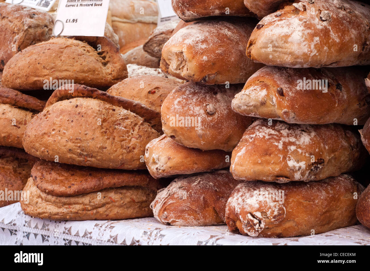Loaves of fresh bread stacked at a Market - Stock Image