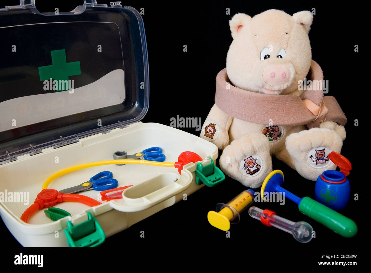 An 'injured'  cuddly toy surrounded by a variety of implements from a child's doctor's kit. - Stock Image
