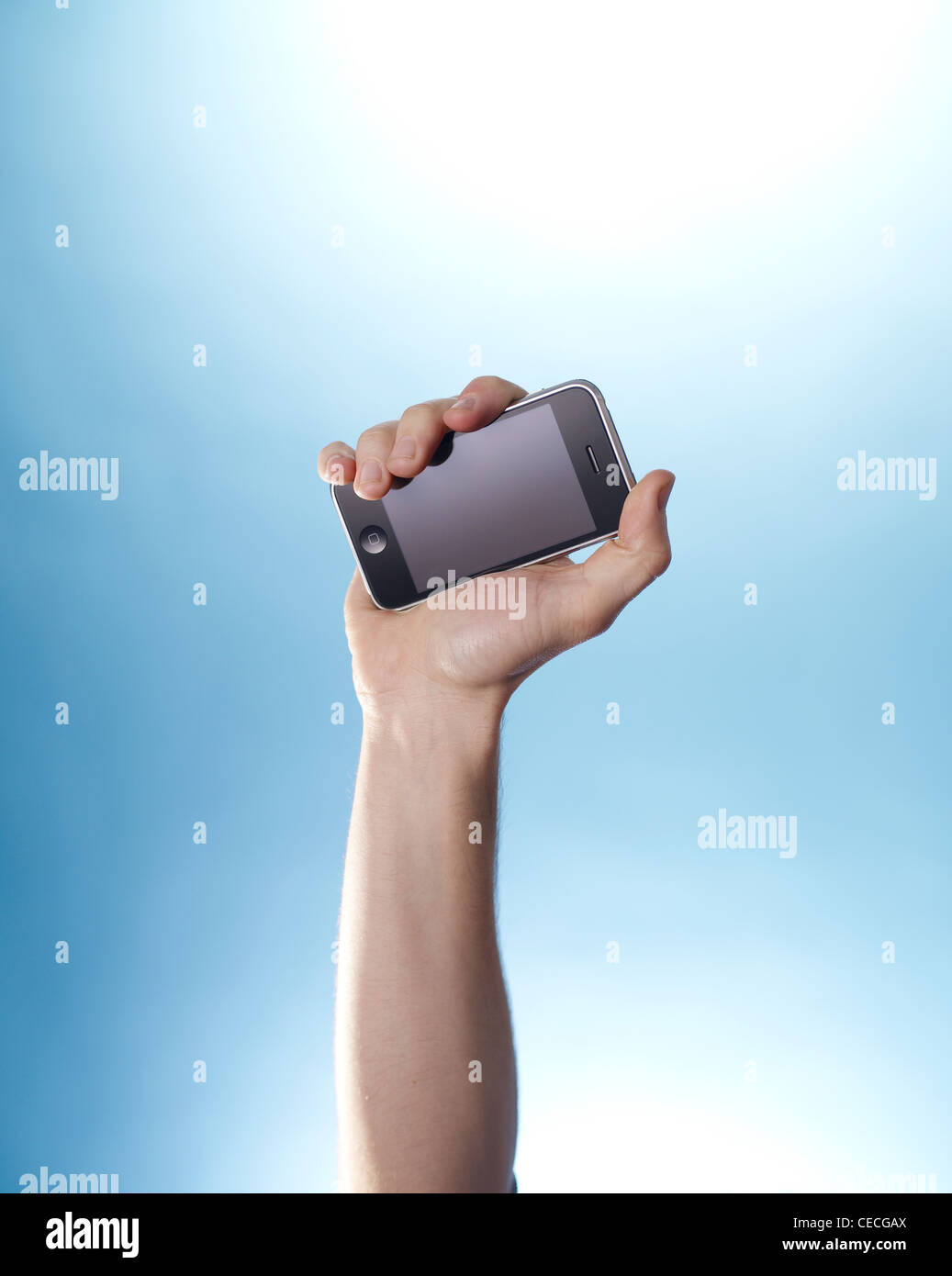 Hand holding an iPhone up against a sky blue background - Stock Image