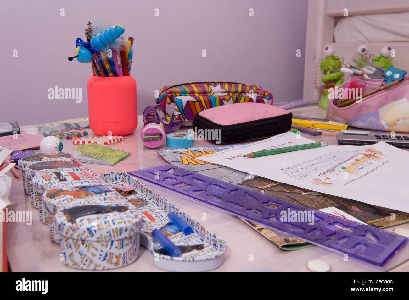 A child's desk, covered in a wide variety of stationery. - Stock Image